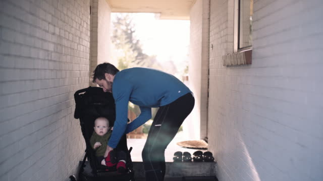 dad puts baby boy in jogging stroller - sportkinderwagen stock-videos und b-roll-filmmaterial
