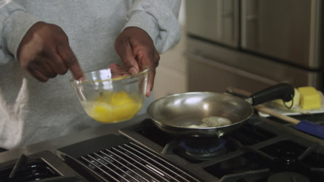 MS TD TU Dad putting butter in skillet then scrambles eggs / Dallas, Texas, USA