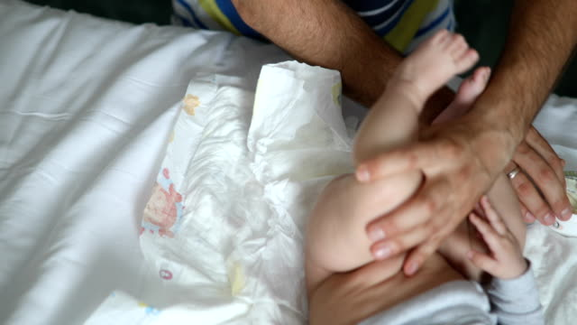 vídeos de stock, filmes e b-roll de pai a pôr creme de fralda na parte inferior do bebê - fralda