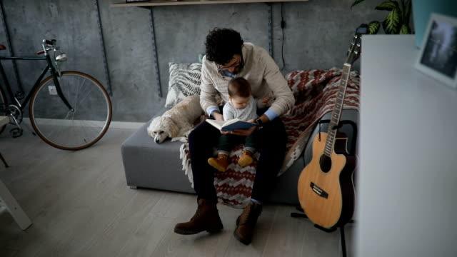 vídeos de stock e filmes b-roll de dad reading stories to his baby boy - pai dono de casa