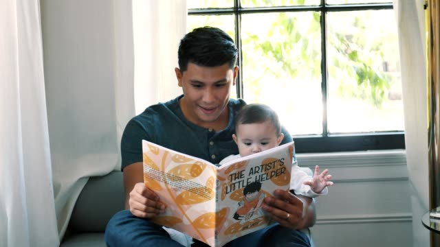 dad reads baby girl a story book - nanny stock videos & royalty-free footage