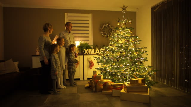 dad ringing bell in front of christmas tree - familie mit drei kindern stock-videos und b-roll-filmmaterial
