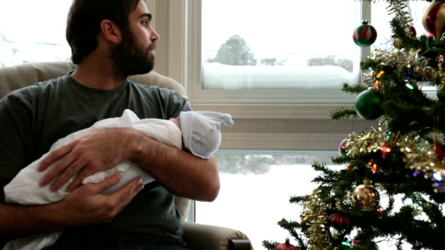 Dad rocking his newborn close to Christmas tree and Snowstorm