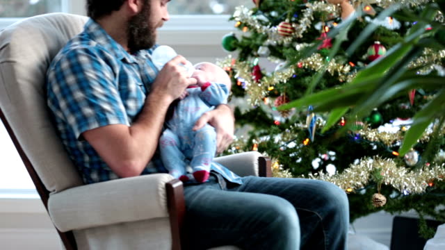 dad rocking his newborn close to christmas tree and snowstorm - dondolarsi video stock e b–roll
