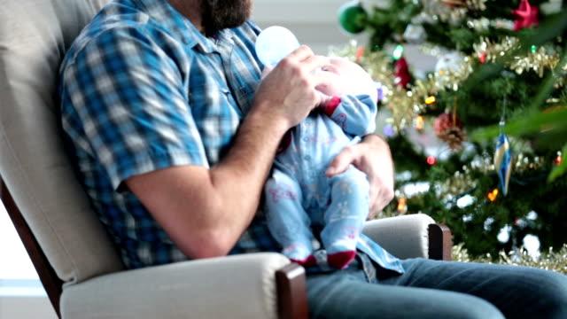 vídeos y material grabado en eventos de stock de papá mecer su recién nacido cerca de árbol de navidad y tormenta de nieve - balancearse