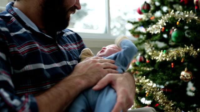 stockvideo's en b-roll-footage met papa zijn pasgeboren dicht bij kerstboom en sneeuwstorm schommelen - schommelen schommelstoel