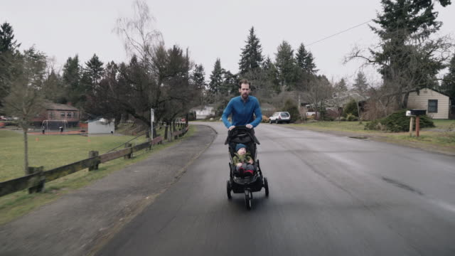 dad runs and pushes baby boy in stroller - three wheeled pushchair stock videos & royalty-free footage