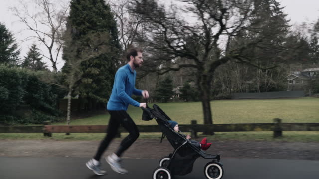 dad runs and pushes baby boy in stroller - jogging stock videos & royalty-free footage