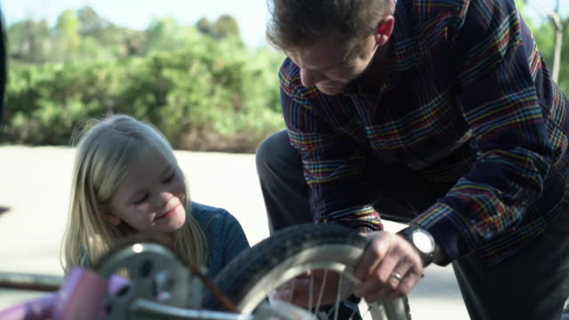 CU Dad showing his daughter how to fix her bike.