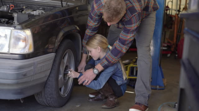 MS Dad showing his daughter how to repair a tire