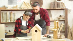 Dad shows his little son how to make birdhouse