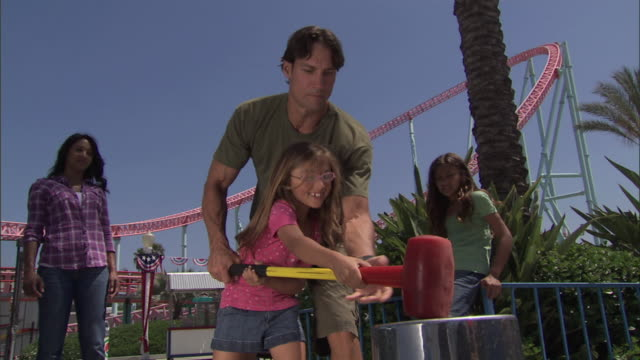 dad shows young girl how to play hi-striker midway game at knott's berry farm - fairground stall stock videos & royalty-free footage