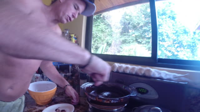 Dad stirs chocolate on stove top at home.
