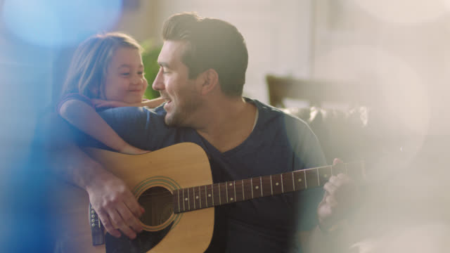 ms. dad strums acoustic guitar in family living room as daughter leans on his shoulder and plays with his hair. - guitar stock videos & royalty-free footage