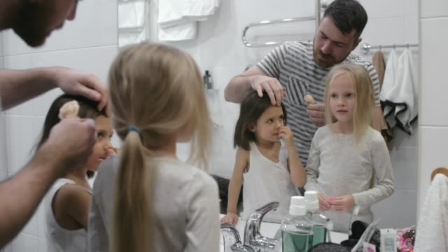 dad styling daughters' hair in the morning - genderblend stock videos & royalty-free footage