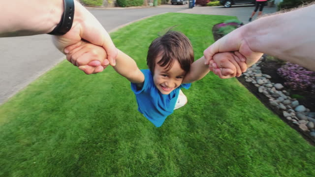 dad swinging his son in circles outside - acrobatic activity stock videos & royalty-free footage
