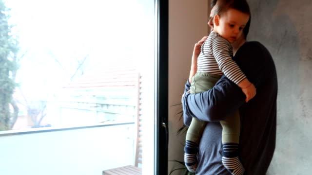 vidéos et rushes de papa parlant au téléphone et tenant son fils de chéri - prendre sur les genoux