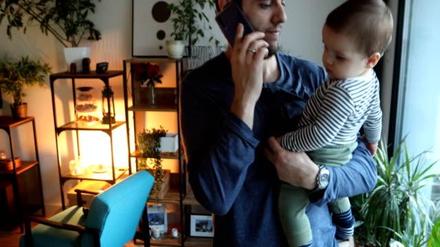 vídeos y material grabado en eventos de stock de papá hablando por teléfono y sosteniendo a su hijo pequeño - genderblend
