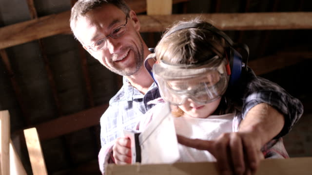 Dad teaches daughter how to saw wood