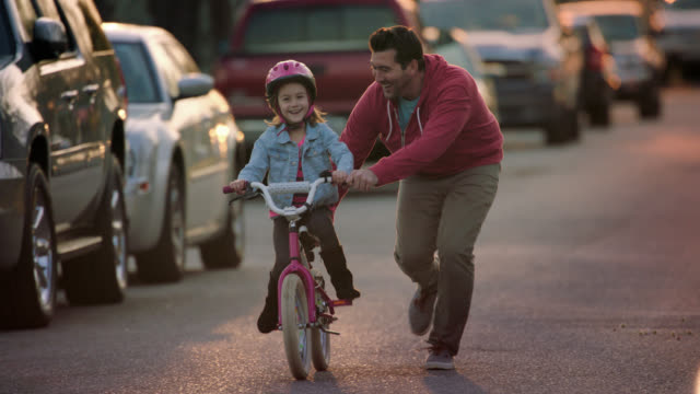 WS SLO MO. Dad teaches daughter to ride bicycle on neighborhood street.