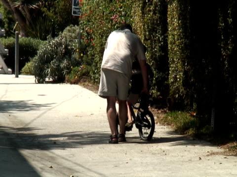 vídeos y material grabado en eventos de stock de dad enseñanza niño andar en bicicleta - intergénero