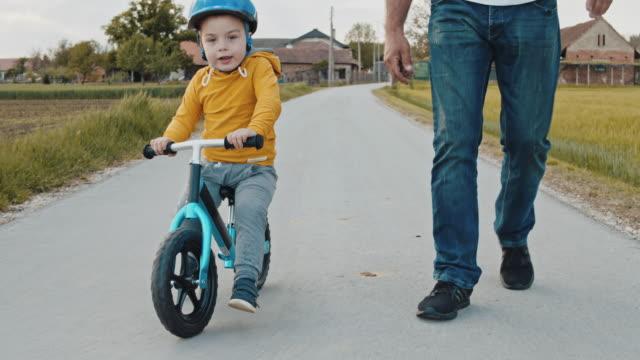 vídeos de stock, filmes e b-roll de ms ts slo mo pai ensinando filho a andar de bicicleta - teaching