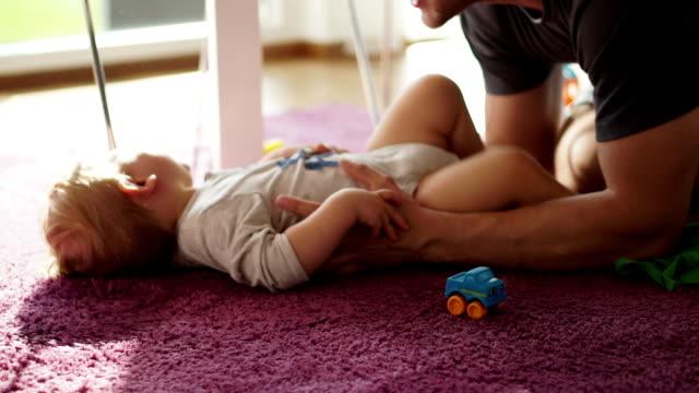 dad tickeling baby boy