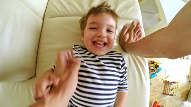 pov dad tickling his small boy on the couch - baby boys stock videos and b-roll footage