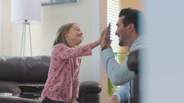 vídeos de stock, filmes e b-roll de ms. dad ties daughter's shoelaces and gives her high five in morning routine. - high five