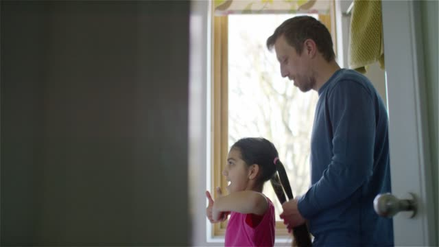 a dad ties his daughter's hair in a pony tail - coda di cavallo video stock e b–roll