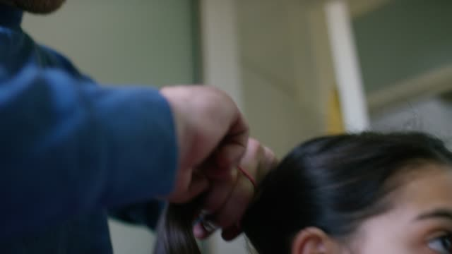 a dad ties his daughter's hair in a pony tail - single father stock videos & royalty-free footage