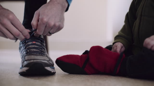 Dad Ties Running Shoes While Baby Boy Watches