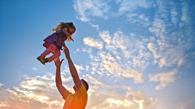 SLO MO Di Vater Herumwerfen Tochter in der Luft bei Sonnenuntergang