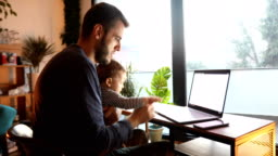 Dad using laptop and holding his baby son