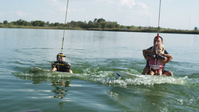 dad wakeboarding with two daughters - waterskiing stock videos & royalty-free footage
