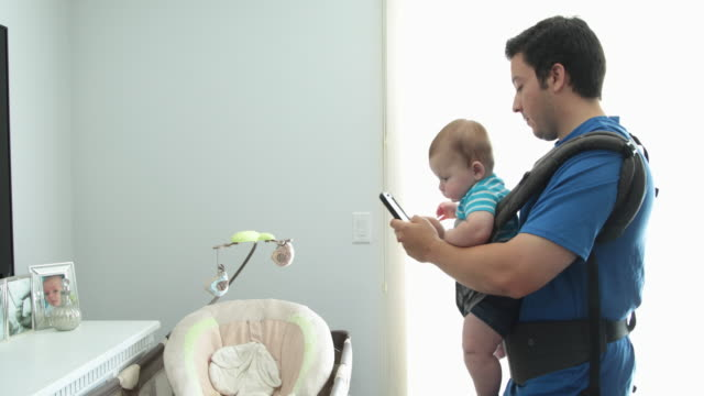 dad with baby in baby carrier pacing the floor checking messages on phone - baby carrier stock videos & royalty-free footage