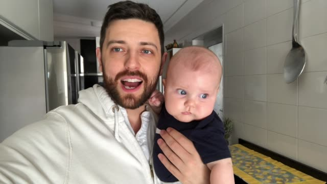 dad with his newborn son doing a video call at home - baby waving stock videos & royalty-free footage
