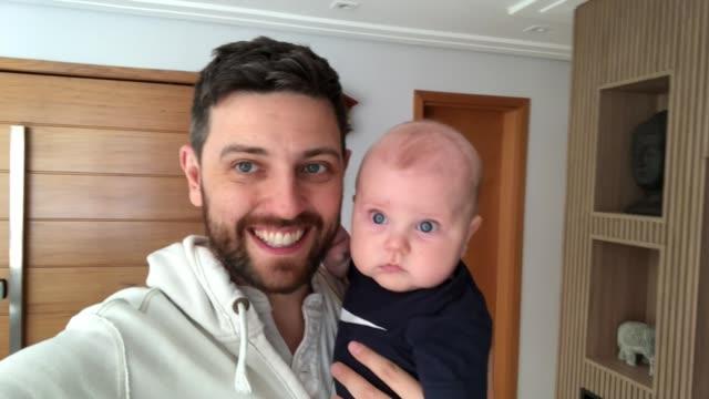 stockvideo's en b-roll-footage met papa met zijn pasgeboren zoon die een videovraag thuis doet - looking at camera