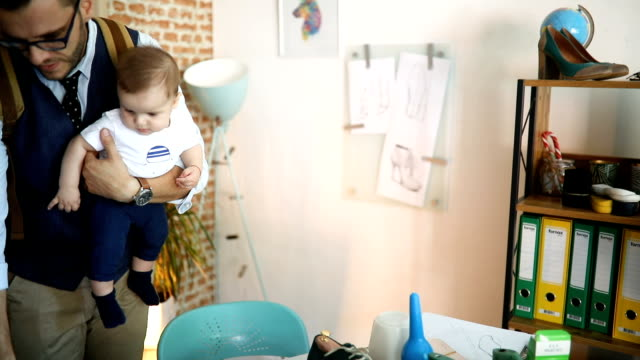 Papa travaille et garde son bébé dans un petit bureau