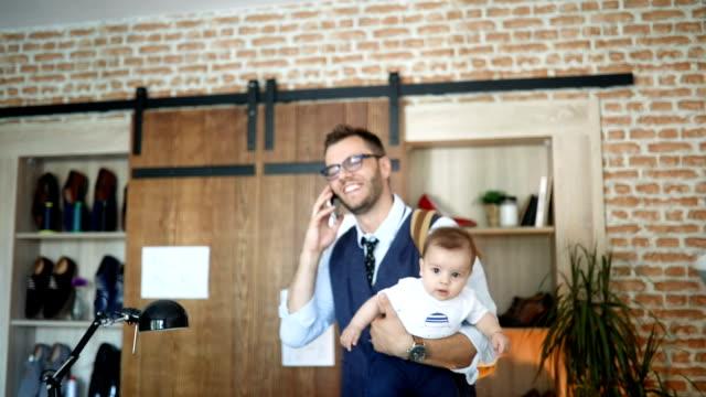 vídeos y material grabado en eventos de stock de papá trabajando y la niñera de su bebé en una oficina pequeña - de origen español o portugués