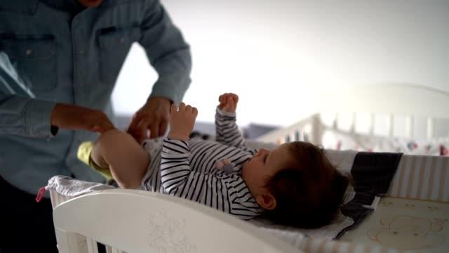 vídeos de stock, filmes e b-roll de papai está cuidando do bebê. - fralda