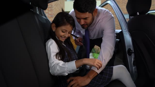 daddy securing her daughter with seat belt in car both smiling - seat belt stock videos & royalty-free footage