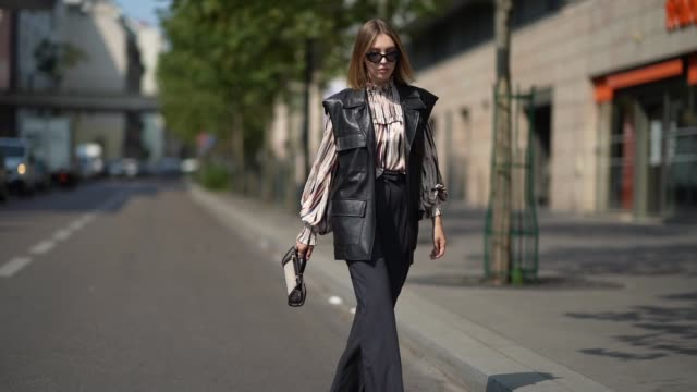 dagmara jarzynka wears sunglasses a munthe striped and ruffled colored top with puff sleeves an oversized sleeveless black leather jacket a tory... - sleeveless top stock videos & royalty-free footage