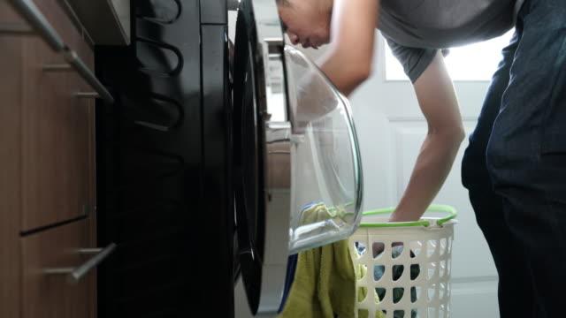 i lavori domestici : uomo di lavanderia in casa - cestino video stock e b–roll
