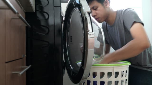 Daily chores: Man laundry at home