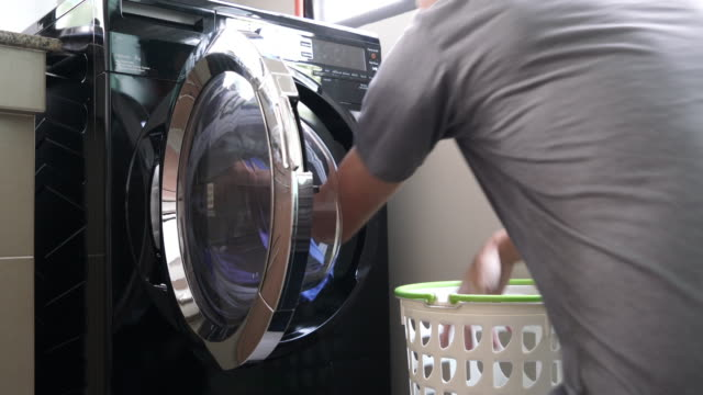 daily chores: man laundry at home - turning on or off stock videos & royalty-free footage