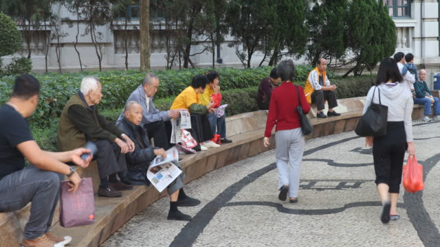 daily life at a square in macau while elderly people sitting and reading newspapers and people walking by - en dag i livet bildbanksvideor och videomaterial från bakom kulisserna