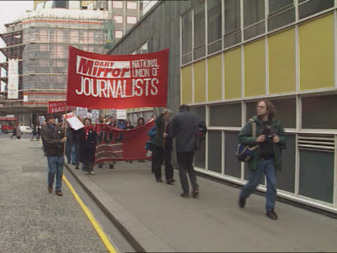 job losses / political direction of paper; england: london: holborn: cms placards being handed out to `daily mirror' workers outside newspaper's hq... - columnist stock videos & royalty-free footage