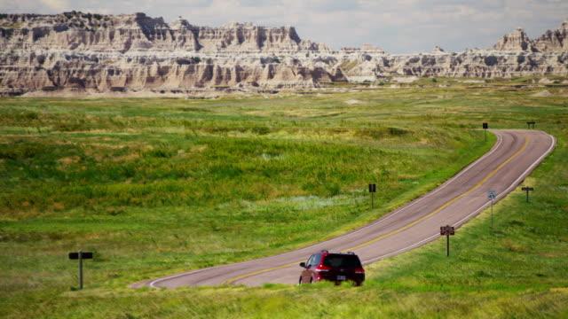 dakota badlands view of vehicle driving desert buttes - 公園保安官点の映像素材/bロール