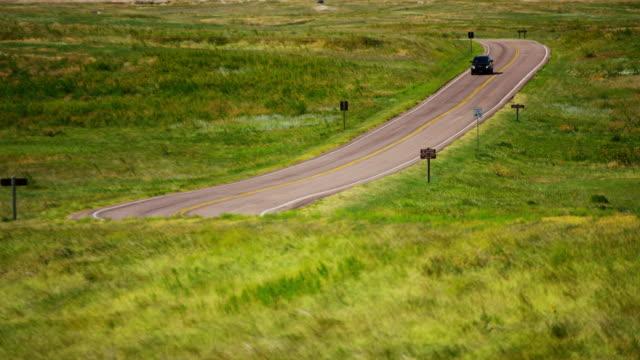 dakota badlands view of vehicle driving desert buttes - south dakota stock-videos und b-roll-filmmaterial
